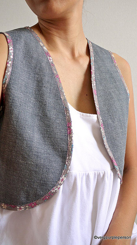 Denim vest with floral bindings